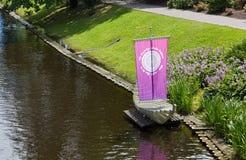 Vorbildliches Sailboat auf der Bank eines Stadt-Kanals in Riga Stockfoto
