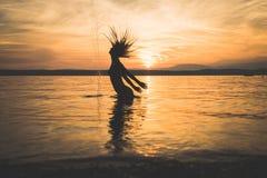 Vorbildliches Schattenbild des jungen attraktiven Mädchens im Wasser stockfotografie