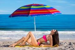 Vorbildliches Sonnen auf dem Strand Stockfoto