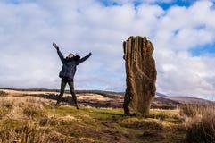Vorbildliches Springen nahe bei einem stehenden Stein in Schottland, Großbritannien. stockbilder