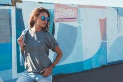 Vorbildliches tragendes einfaches T-Shirt und Sonnenbrille, die über der Straße wal aufwirft stockbilder