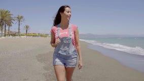 Vorderansicht über Dame, die entlang Strand geht stock footage