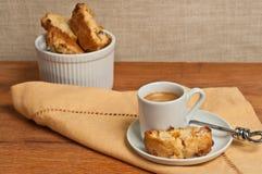 Vorderansicht, Abschluss oben von selbst gemachtem, backte frisch, Aprikosenwalnuß biscotti und Schale Espresso Stockbild