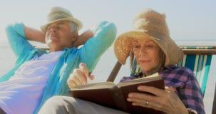 Vorderansicht der aktiven älteren kaukasischen Frau, die ein Buch auf dem Strand 4k liest stock video
