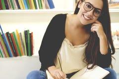 Vorderansicht der Frau lächelnd auf Bibliotheksboden Lizenzfreies Stockfoto