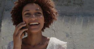 Vorderansicht der jungen Afroamerikanerfrau, die am Handy am Strand im Sonnenschein 4k spricht stock footage