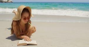 Vorderansicht der kaukasischen Frau im Hut ein Buch auf dem Strand 4k lesend stock video