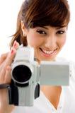 Vorderansicht der lächelnden weiblichen Holding-Videokamera Lizenzfreies Stockbild