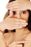 Vorderansicht der nackten Frau ihr Gesicht bedeckend
