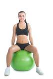 Vorderansicht der netten sportlichen Frau, die auf einem Übungsball sitzt Lizenzfreies Stockbild