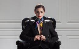 Vorderansicht der strengen Geschäftsfrau im schwarzen Anzug, der im Bos sitzt Stockfotografie