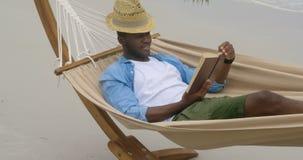 Vorderansicht des Afroamerikanermannes ein Buch auf dem Strand 4k lesend stock footage