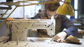 Vorderansicht des amerikanischen Experten macht Lederware am Schreibtisch, wenn sie Innenraum beleuchtet stock footage