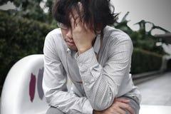 Vorderansicht des frustrierten betonten jungen asiatischen Geschäftsmannes mit den Händen, die Kopf berühren und enttäuscht oder  Lizenzfreie Stockbilder
