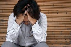 Vorderansicht des frustrierten betonten jungen asiatischen Geschäftsmannes mit den Händen, die Kopf berühren und enttäuscht oder  Lizenzfreies Stockfoto