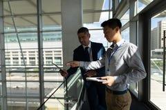 Vorderansicht des Geschäftsmannes aufeinander einwirkend über digitale Tablette auf dem ersten Stockwerk des Büros stockfotos