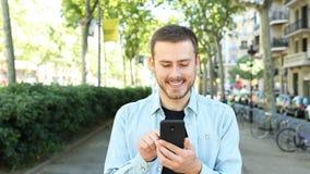 Vorderansicht des glücklichen Mannes unter Verwendung des Telefons in der Straße