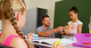 Vorderansicht des jungen kaukasischen männlichen Lehrers, der in der Schule anatomisches Modell im Klassenzimmer 4k erklärt stock video