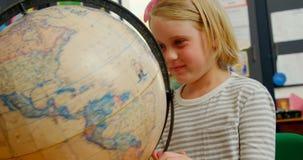 Vorderansicht des kaukasischen Schulmädchens Kugel am Schreibtisch im Klassenzimmer 4k in der Schule studierend stock footage