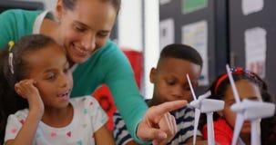 Vorderansicht des kaukasischen Unterrichtsstudenten des weiblichen Lehrers über Windmühle im Klassenzimmer 4k stock video footage