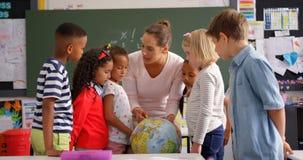 Vorderansicht des kaukasischen weiblichen Lehrers, der ?ber Kugel im Klassenzimmer 4k erkl?rt stock footage