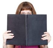 Vorderansicht des Mädchens mit Schauspielen schaut über Buch Stockbilder