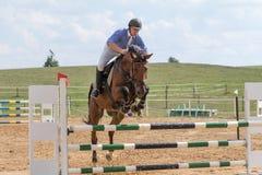 Vorderansicht des Reiters im blauem Springen auf ein Pferd Stockbild