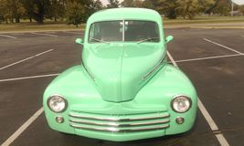 Vorderansicht des tadellosen grünen antiken Fahrzeugs Stockfotos