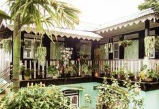 Vorderansicht des Vorstadthauses mit manikürtem Blumengarten Schöner Landschaftsentwurf der Familiendekoration mit Sträuchen, Fic lizenzfreies stockbild