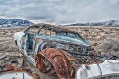 Vorderansicht eines alten verlassenen Autos und der Teile in der Wüste Stockfotografie