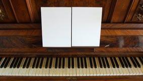 Vorderansicht eines antiken Klaviers mit der Tastatur offen und zwei Blättern Papier leeres Papier auf Unterstützung für musikali Stockbild