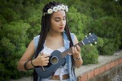 Vorderansicht eines jungen schönen Mädchens mit dem umsponnenen Haar, die Ukulele spielend stockfotografie