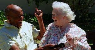 Vorderansicht von älteren Paaren der aktiven Mischrasse unter Verwendung des Handys im Garten des Pflegeheims 4k stock footage