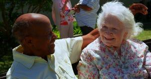 Vorderansicht von den älteren Paaren der aktiven Mischrasse, die im Garten des Pflegeheims 4k sich umfassen stock footage