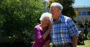 Vorderansicht von den aktiven kaukasischen älteren Paaren, die in den Garten des Pflegeheims 4k gehen stock video