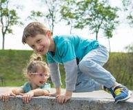 Vorderansicht von den Kindern, die Zeit im Stadtpark, -jungen und -m?dchen sitzen auf dem Stein verbringen Gl?cklicher l?chelnder lizenzfreie stockfotos