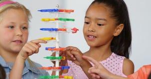 Vorderansicht von den Mischrasseschulkindern, die über DNS-Struktur im Klassenzimmer 4k studieren stock video footage