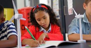 Vorderansicht von den Mischrasseschulkindern, die am Schreibtisch im Klassenzimmer 4k studieren stock footage
