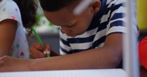 Vorderansicht von den Mischrasseschulkindern, die am Schreibtisch im Klassenzimmer 4k studieren stock video