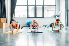 Vorderansicht von den multiethnischen weiblichen Athleten, die Planke auf Eignungsmatten tun stockbild