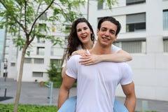 Vorderansicht von den schönen jungen umarmenden, Kamera betrachtenden und bei draußen stehen lächelnden Paaren lizenzfreies stockbild