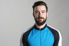 Vorderansichtporträt des lächelnden tragenden Radfahrentrikott-shirts des glücklichen Radfahrers Lizenzfreie Stockbilder