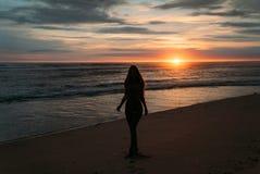 Vorderansichtschattenbild der attraktiven Frau Schönes junges Mädchen mit dem langen Haar gehend auf den Strand, werfend bei Sonn Stockfoto