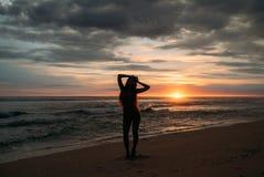Vorderansichtschattenbild der attraktiven Frau Schönes junges Mädchen mit dem langen Haar gehend auf den Strand, werfend bei Sonn Lizenzfreie Stockfotografie