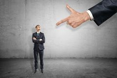 Vordere Ansicht in voller L?nge Kleinunternehmers, der oben der riesigen Hand zeigt Zeigefinger auf ihn steht und betrachtet lizenzfreies stockfoto