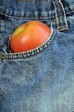 Vordere Blue Jeanstasche, die einen Apfel anhält Stockbilder