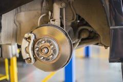 Vordere Plattenbremse auf Auto im Prozess des geschädigten Reifenersatzes Stockfotografie