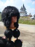 Vordergrund eines charakteristischen Pelzhutes von Rumänien mit Pompoms zur Extremität und traditionellen Kirchen im Abstand Lizenzfreie Stockbilder
