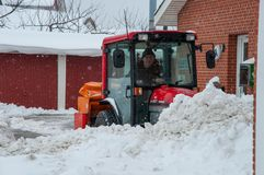 Worker on a tractor plowing snow after a Blizzard Stock Images