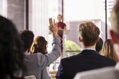 Vorführer auf Geschäftsseminar bringt eine Frage vom Publikum vor lizenzfreies stockfoto